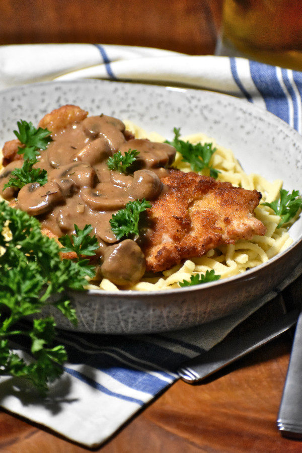 jagerschnitzel on a bed of spaetzel in a rustic bowl garnished with fresh parsley