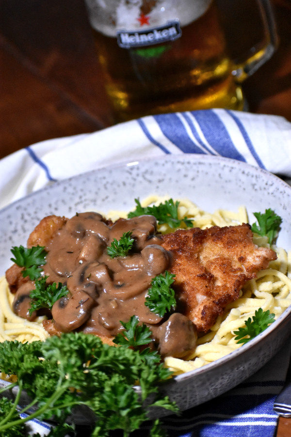 jagerschnitzel on a bed of spaetzel in a rustic bowl, with a stein of beer in the background