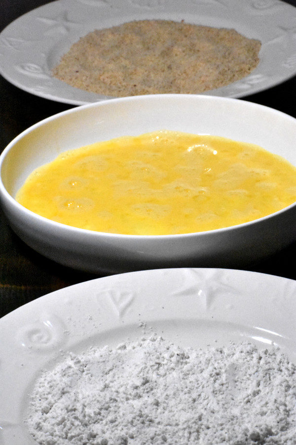 three dishes lines up with flour, beaten eggs and breadcrumbs
