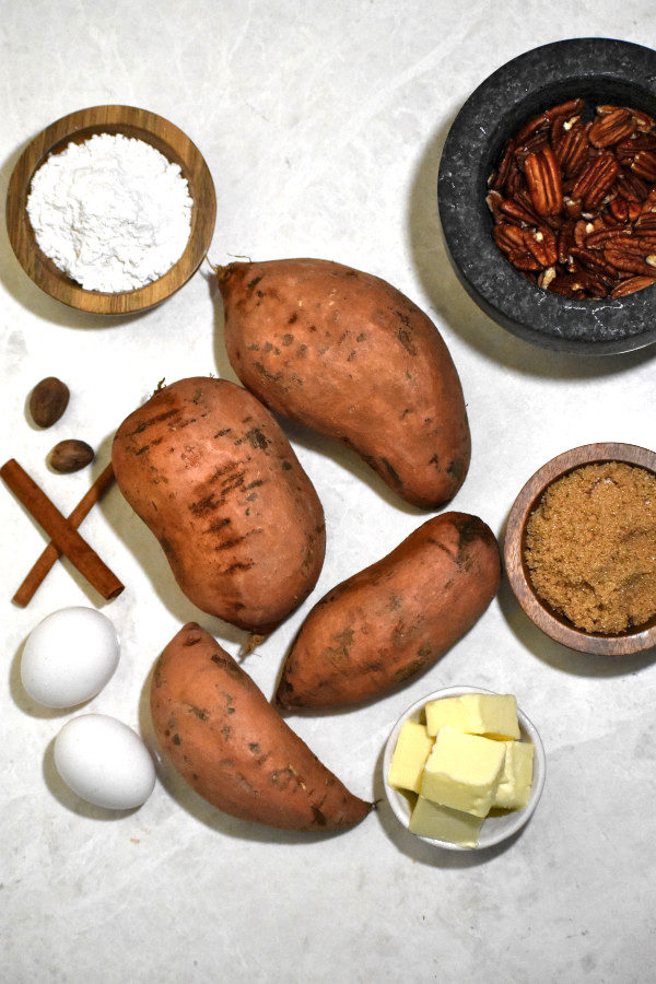 overhead ingredient shot with sweet potatoes, eggs, butter, flour, brown sugar, cinnamon sticks, whole nutmeg and pecans on a marble background