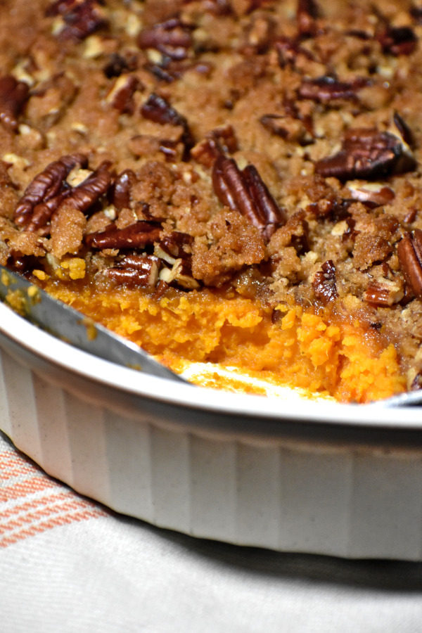 view of sweet potato casserole that has had a pice scooped out, pecan streusel visible on top