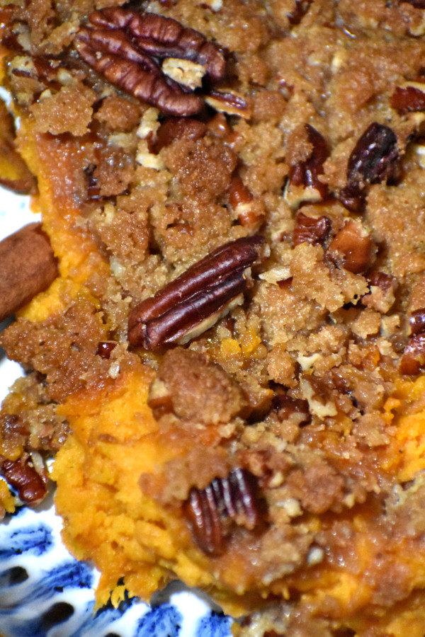 extreme close up of sweet potato casserole with pecan streusel in a blue bowl