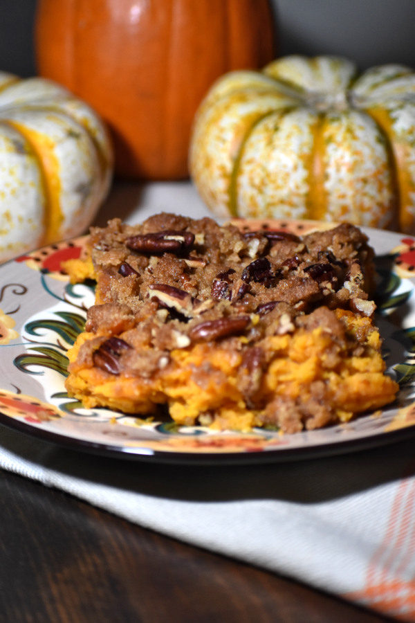 side view of sweet potato casserole with pecan streusel on the gypsy plate with miniature pumpkins in the background
