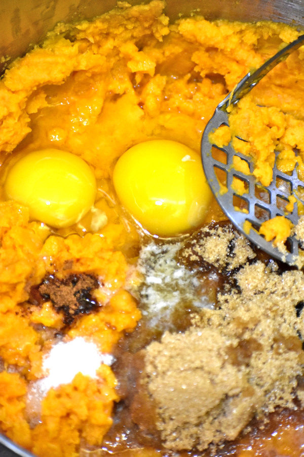 mashed sweet potatoes in a large pan with brown sugar, cinnamon, salt and two cracked eggs added on top with masher on the side