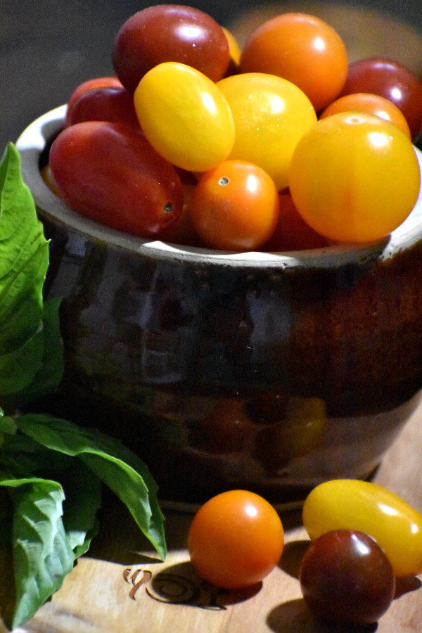 side view of multi colored cherry tomatoes in a brown bowl with a sprig of basil to the left
