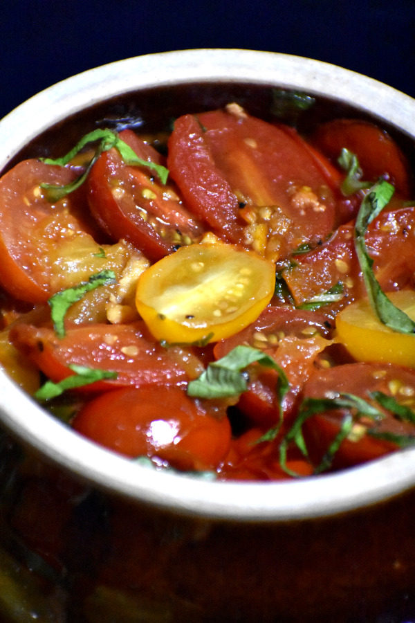 close up shot of cooked tomatoes with orange marmalade in a brown bowl