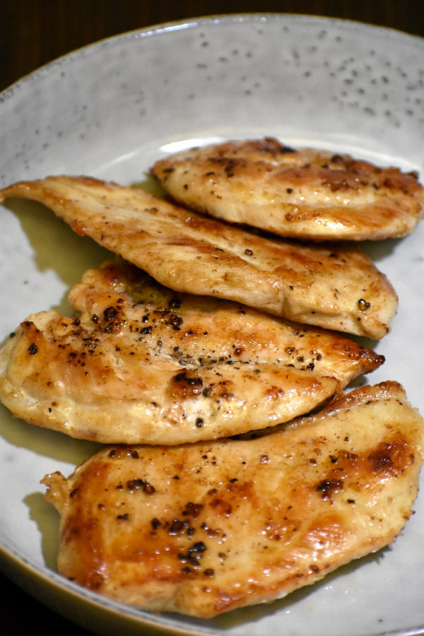 cooked butterflied chicken breasts in a grey dish