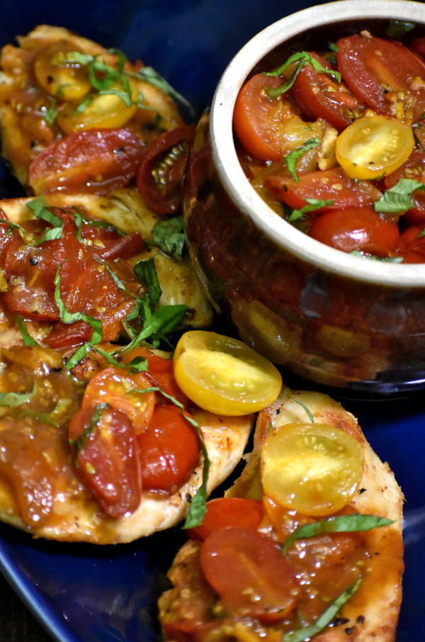 over head picture of tomato basil chicken on a blue platter