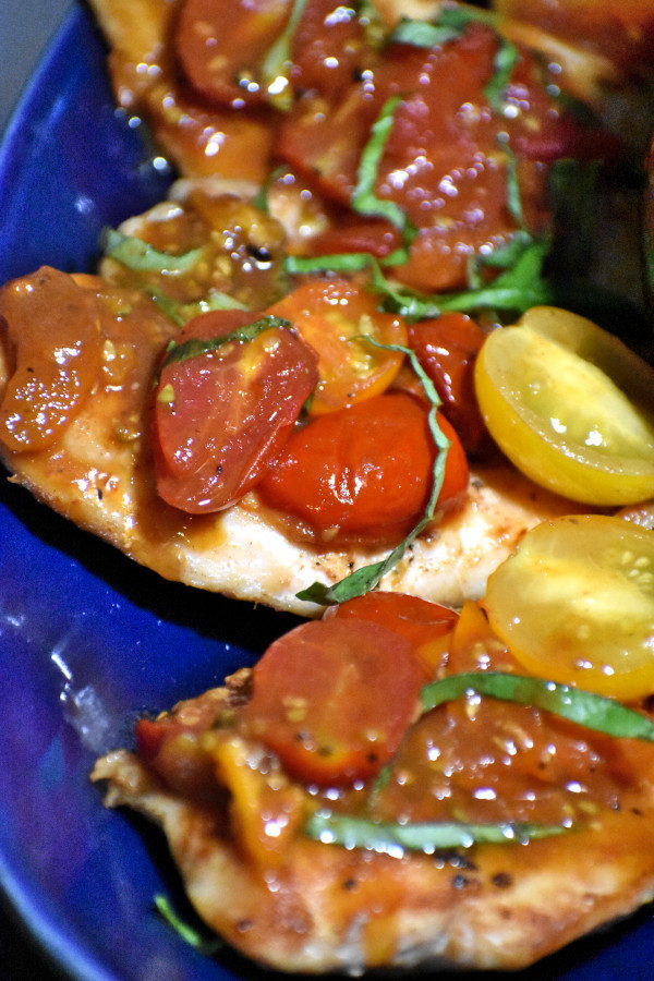 close up side view of tomato basil chicken on a blue platter