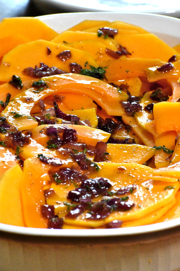 slices of butternut squash topped with cooked red onions and thyme in a white dish