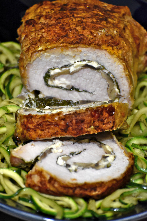 stuffed pork loin with two pinwheels cut from it atop a bed of zucchinicci