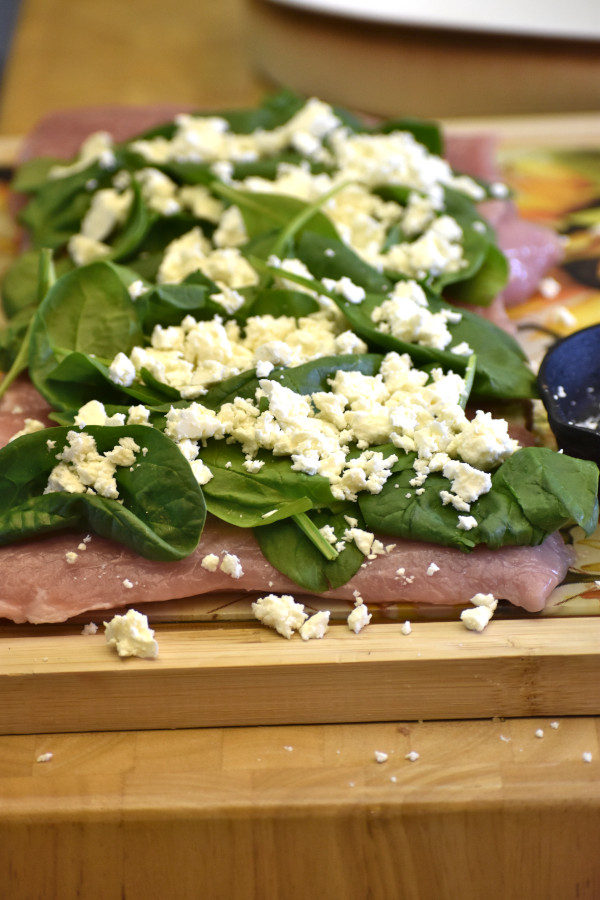 45 degree view of butterflied pork loin topped with spinach and feta cheese