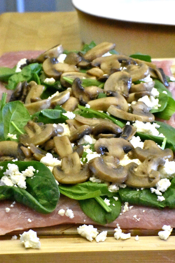 45 degree view of butterflied pork loin topped with spinach, feta cheese and mushrooms