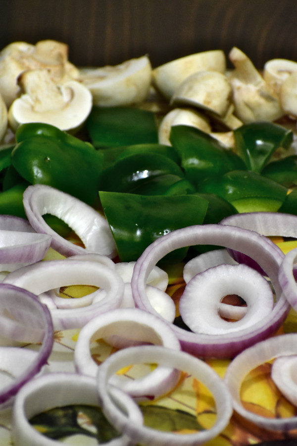 side view of chopped onions, green bell peppers and mushrooms