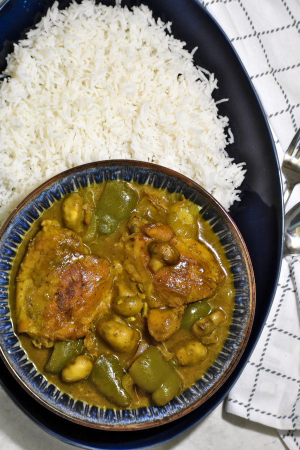 overhead shot of a blue bowl full of south african chicken curry on a large blue platter with rice. to the right is a white napkin and spoon and fork.