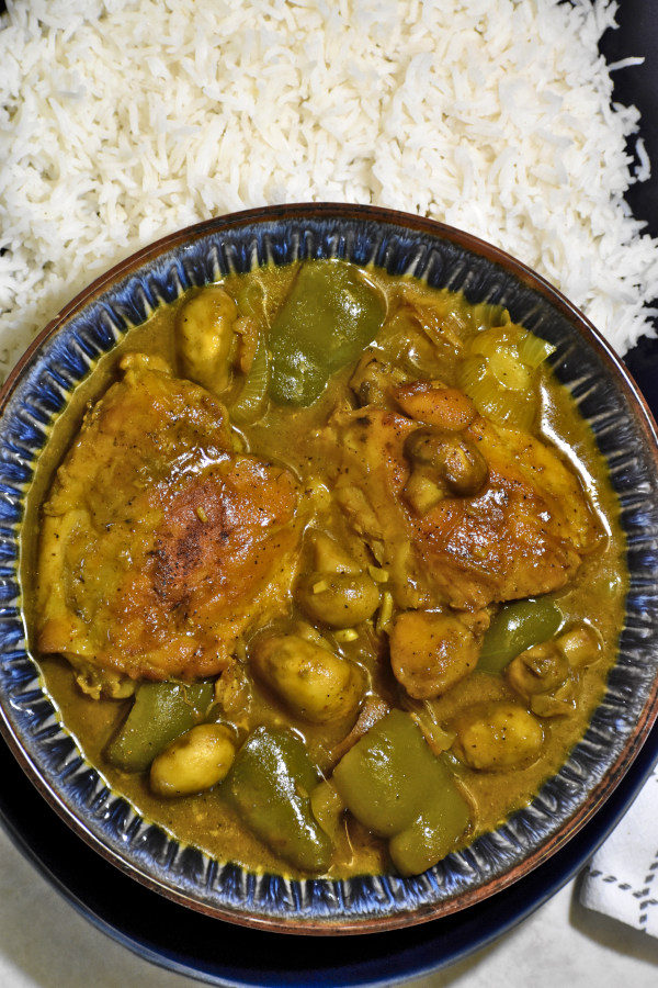 overhead shot of blue bowl full of south african chicken curry with rice above