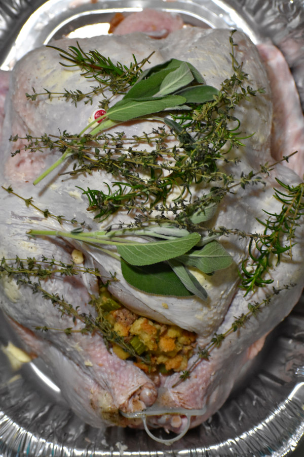 stuffed raw turkey in aluminum pan topped with fresh thyme, sage and rosemary