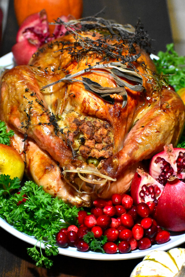 end view of roasted turkey on a white platter and garnished with fresh cranberries, sliced pomegranate, pears, sage and parsley