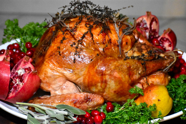 side view of roasted turkey on a white platter and garnished with fresh cranberries, sliced pomegranate, a pear, sage and parsley