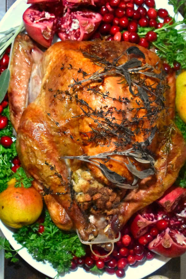 overhead view of roasted turkey on a white platter and garnished with fresh cranberries, sliced pomegranate, pears, sage and parsley