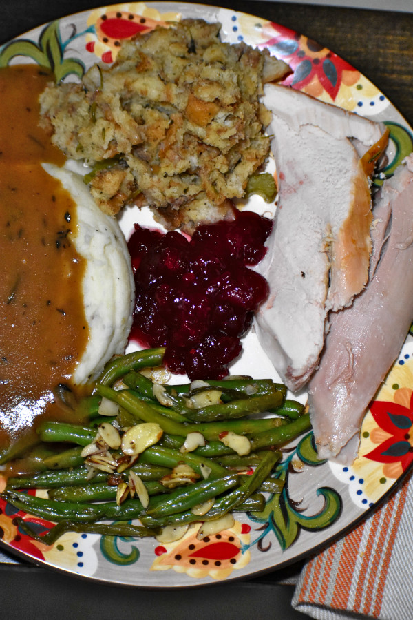 sliced turkey, stuffing, green beans, gravy topped mashed potatoes and cranberry sauce on the gypsy plate
