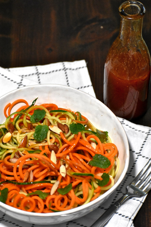spiralized carrots and zucchini mixed with catalina dressing in a white bowl garnished with slivered almonds and mint leaves. the bowl is atop a white napkin and there is a bottle of dressing beside.