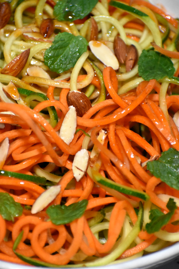 close up view of spiralized carrots and zucchini mixed with catalina dressing in a white bowl garnished with slivered almonds and mint leaves