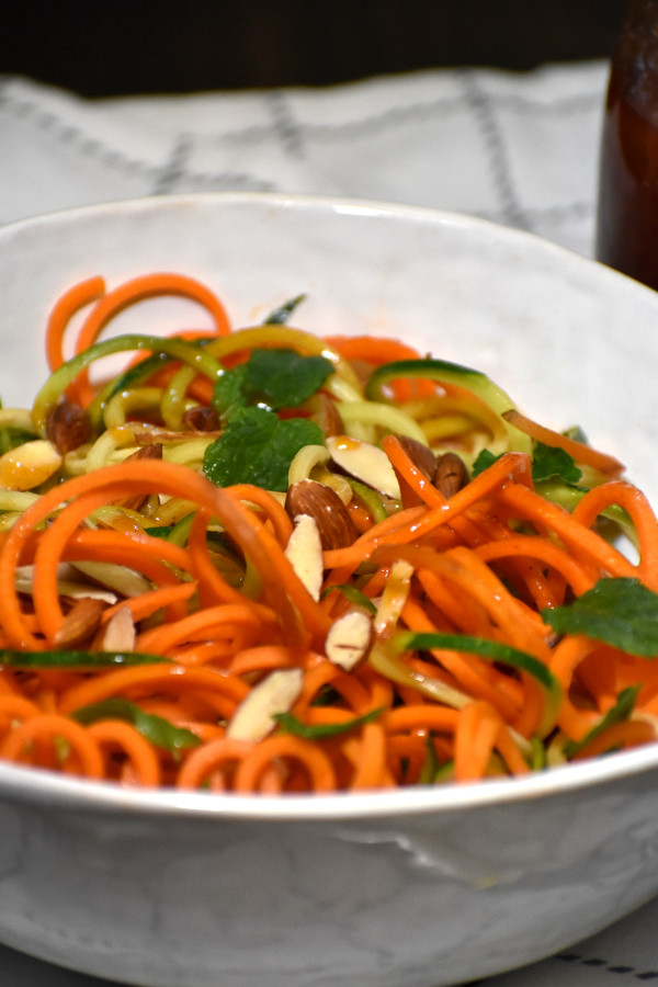 side view of spiralized carrots and zucchini mixed with catalina dressing in a white bowl garnished with slivered almonds and mint leaves