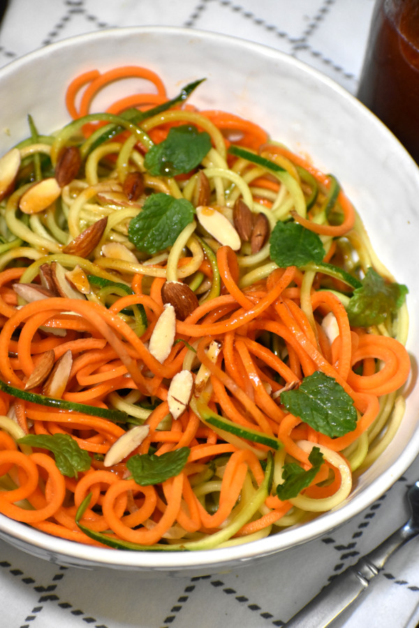 spiralized carrots and zucchini mixed with catalina dressing in a white bowl garnished with slivered almonds and mint leaves