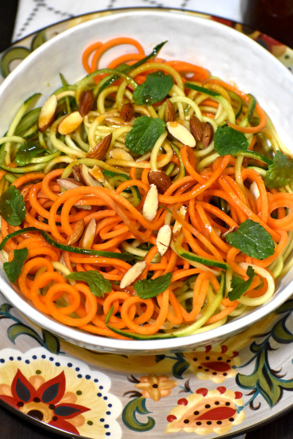 spiralized carrots and zucchini mixed with catalina dressing in a white bowl garnished with slivered almonds and mint leaves. the bowl is atop the gypsy plate.