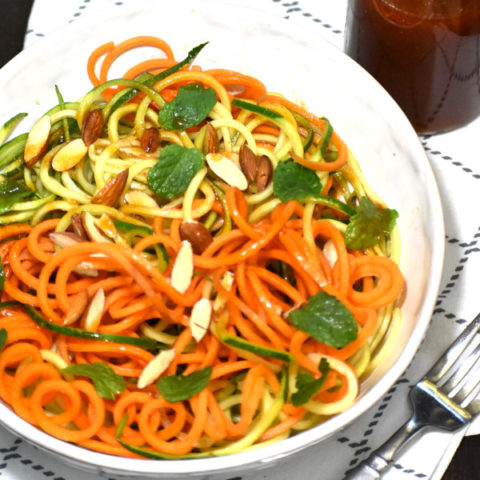 spiralized carrots and zucchini mixed with catalina dressing in a white bowl garnished with slivered almonds and mint leaveszicchini carrot salad with catalina dressing in a white bowl sitting on a white napkin next to a glass container full of catalina dressing