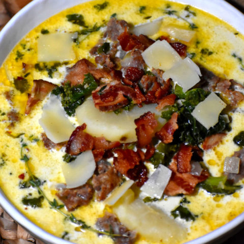 close up shot of zuppa toscana in a white bown garnished with crumbled bacon and sausage and shaved parmesan cheese