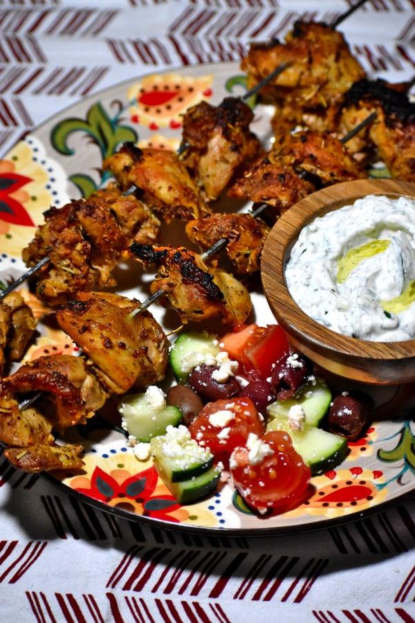 a dish of tzatziki, alongside souvlaki chicken kebabs, on the gypsy plate