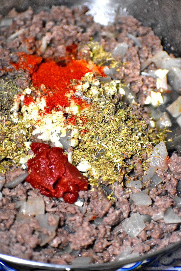 spices and tomato paste added to cooked ground beef
