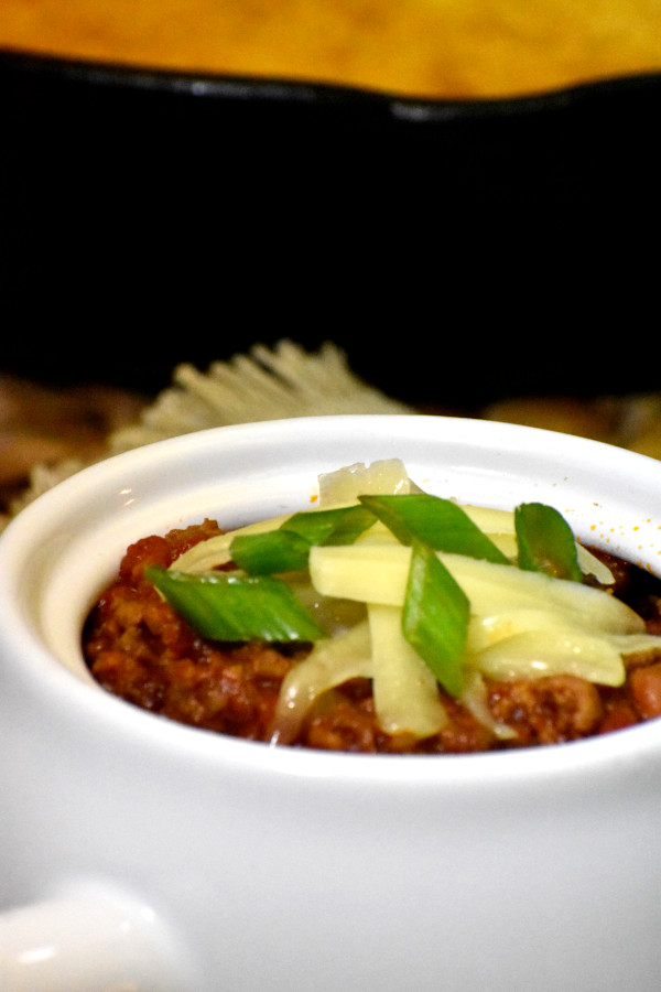 smoky chipotle chili in a white bowl garnished with shredded cheddar cheese and diced green onions