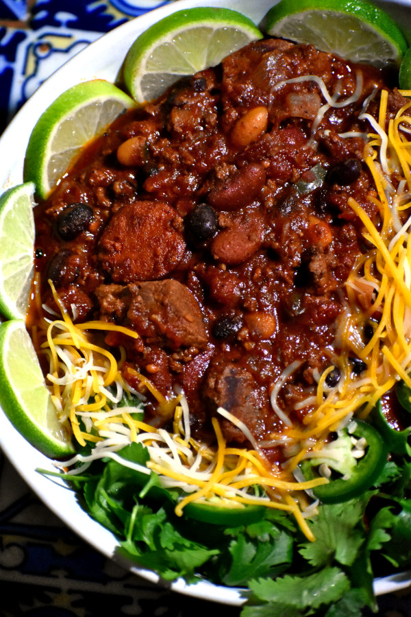 The ultimate chili in a bowl garnished with shredded cheese, cilantro and diced jalepenos