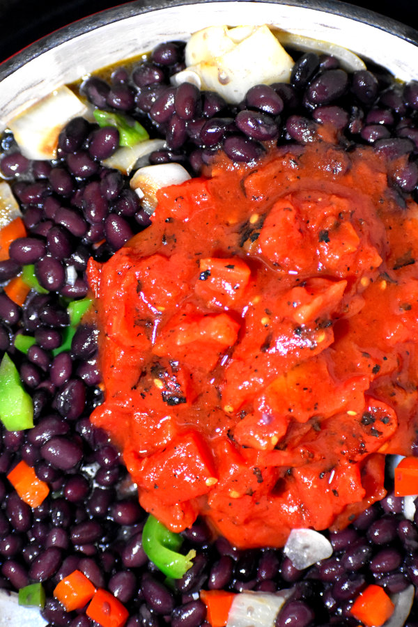 black beans and tomatoes added to cooked onions and peppers