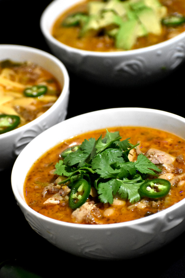 white bean turkey chili in three different bowls with different garnishings