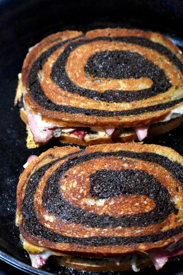 reuben sandwiches in a cast iron skillet