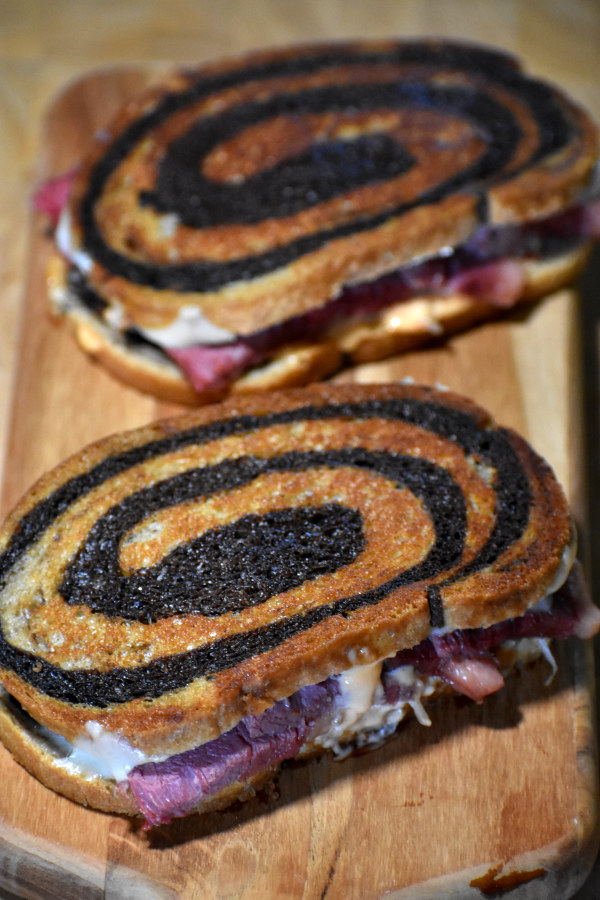 two reuben sandwiches on a wooden cutting board