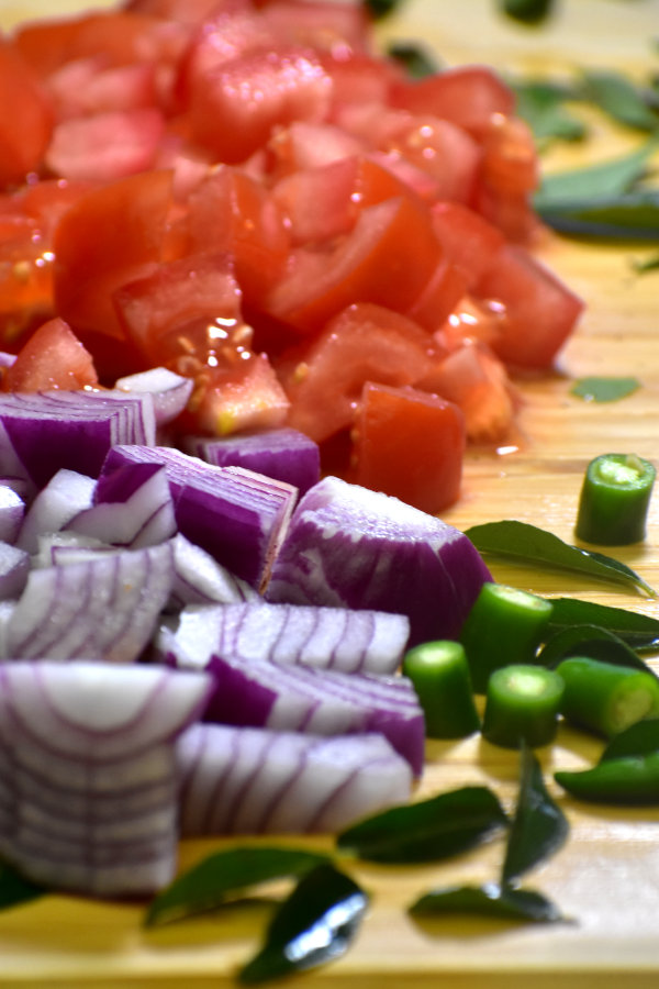 chopped onions, tomatoes and green chilis on a cutting board
