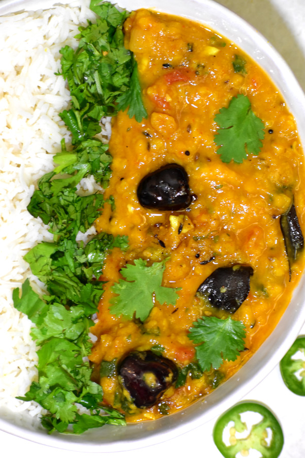 dal and rice garnished with cilantro, in a white bowl