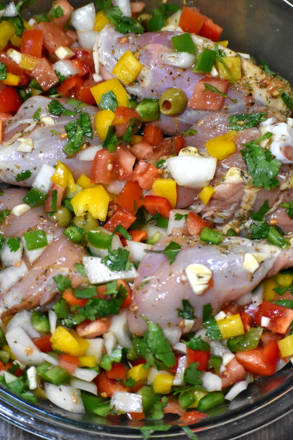 chicken marinating with chopped veggies in a bowl