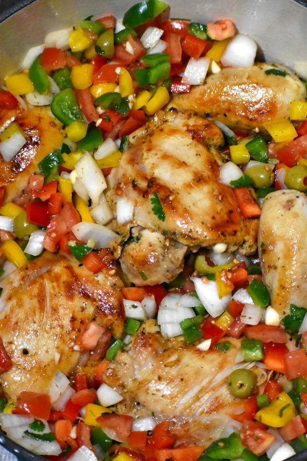 browned chicken and chopped veggies in a pot