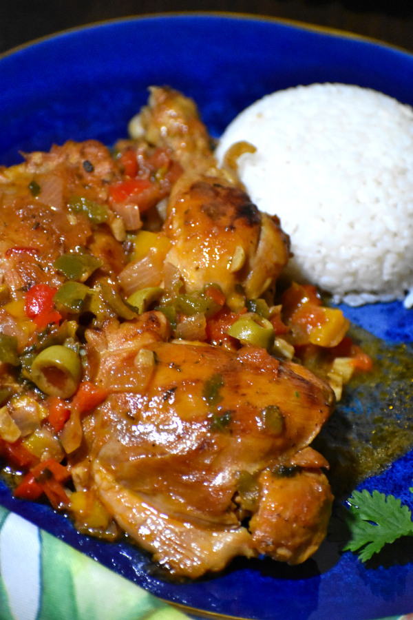 pollo guisado alongside a scoop of white rice on a blue plate