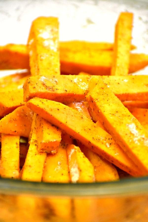 uncooked sweet potatoes fries with seasonings sprinkled on