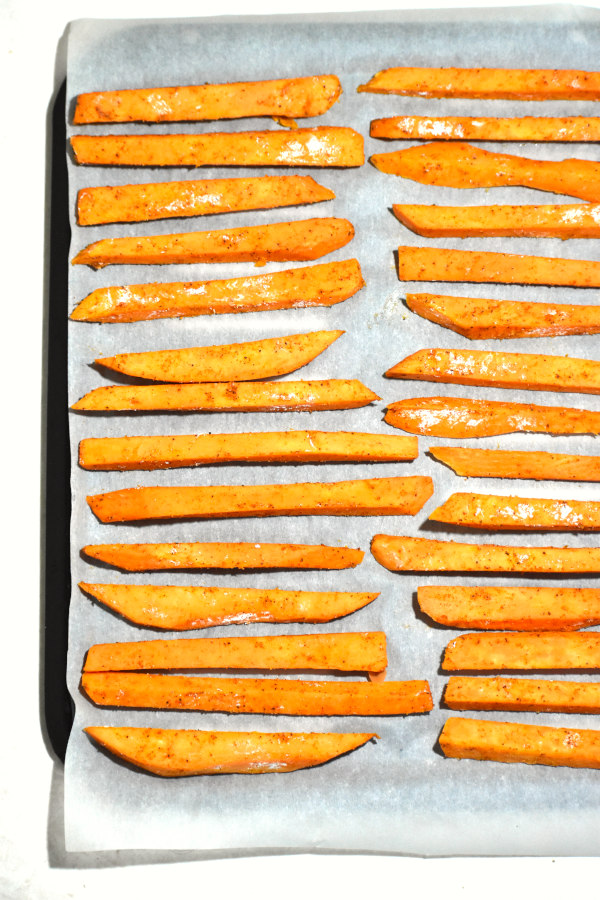 raw sweet potato fries layed out on a parchment paper covered baking sheet