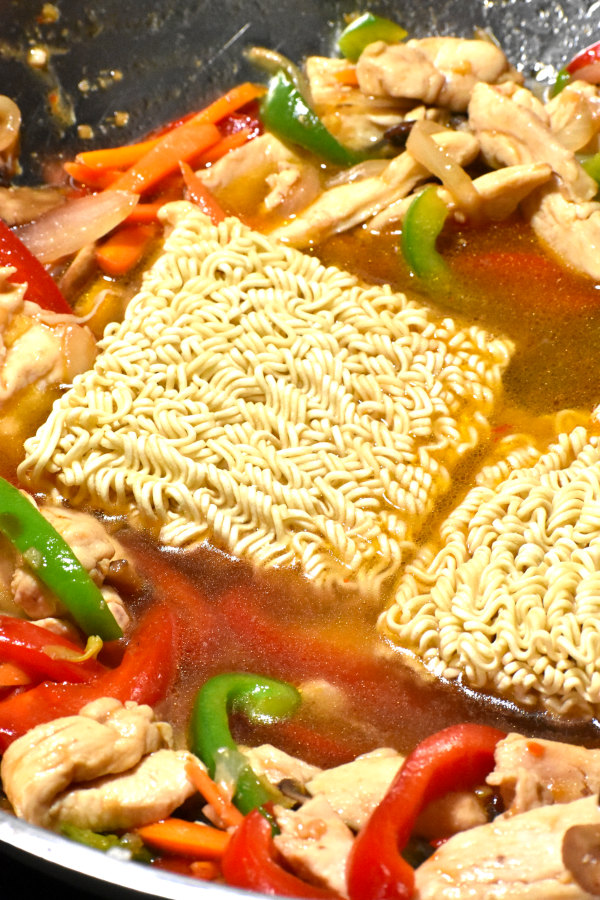 two bricks of ramen noodles added to the pot