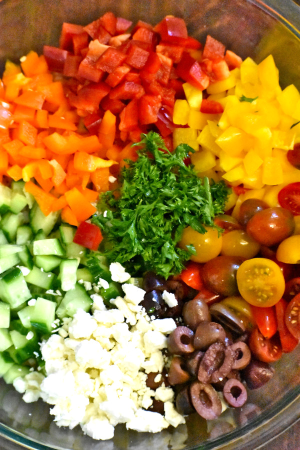 veggies, feta cheese, olives and parley nicely arranged in a bowl