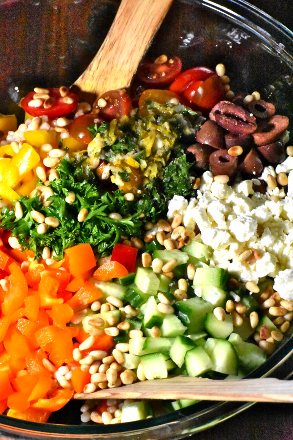 veggies, feta cheese, olives and parley nicely arranged in a bowl with dressing added in